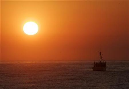 A fishing trawler is seen off Manly Beach in Sydney as the sun rises October 3, 2007. REUTERS/Will Burgess