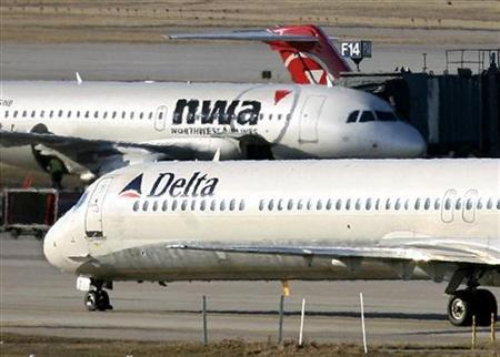 A Delta Air Lines jet taxis past a Northwest Airlines jet parked at a gate at the Minneapolis St.Paul International Airport in Minnesota April 14, 2008. REUTERS/Eric Miller
