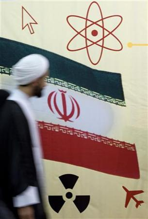 A cleric walks past the national flag and a nuclear logo while visiting the International Koran exhibition at the Imam Khomeini grand mosque in Tehran September 3, 2008. REUTERS/Morteza Nikoubazl
