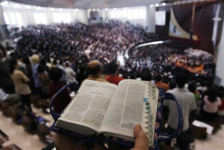 A Christian reads a bible during the opening of the grand Katedral Mesias in Jakarta September 20, 2008. REUTERS/Enny Nuraheni