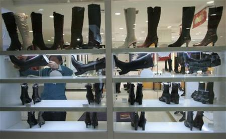A shop assistant arranges leather shoes inside a store in Xining, northwestern China's Qinghai province November 25, 2006. Italian and other shoemakers threatened legal action against the European Commission on Saturday if the EU executive decides to scrap anti-dumping duties on imports of Chinese and Vietnamese leather footwear. REUTERS/Simon Zo
