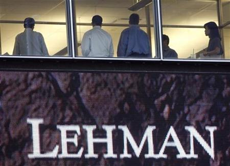 People stand next to windows, above an animated sign, at the Lehman Brothers headquarters in New York September 16, 2008. REUTERS/Chip East