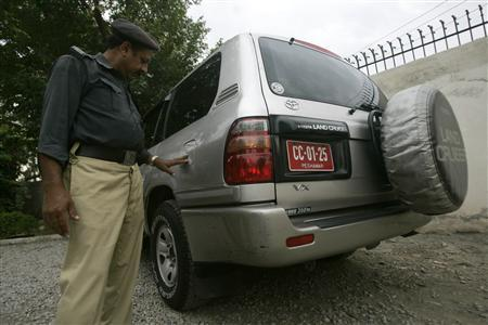 A policeman stands near the vehicle of Afghan diplomat Abdul Khaliq Farahi who was kidnapped by gunmen in Peshawar, September 22, 2008. REUTERS/Ali Imam