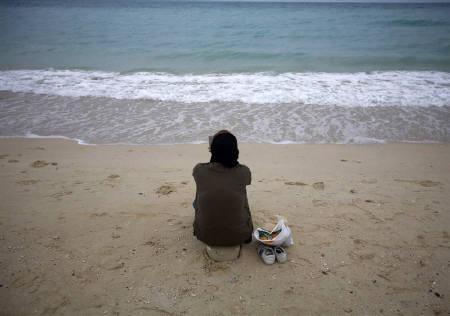 An Iranian woman sits on the southern beach on the island of Kish in the Persian Gulf 1250 km south of Tehran August 4, 2008. REUTERS/Morteza Nikoubazl