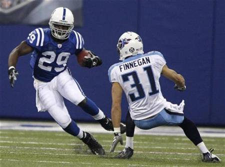 Indianapolis Colts running back Joseph Addai (29) eludes Tennessee Titans defensive back Cortland Finnegan during first quarter play in Indianapolis, December 30, 2007. REUTERS/Brent Smith