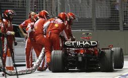 <p>Mecânicos da Ferrari tentam soltar o tubo de combustível da Ferrari de Felipe Massa, durante GP de Cingapura, no domingo. REUTERS/Eugene Hoshiko/Pool</p>