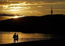 <p>A couple looks towards the Black Mountain Tower as they watch the setting sun over Canberra's Lake Burley Griffin April 23, 2008. REUTERS/Tim Wimborne</p>