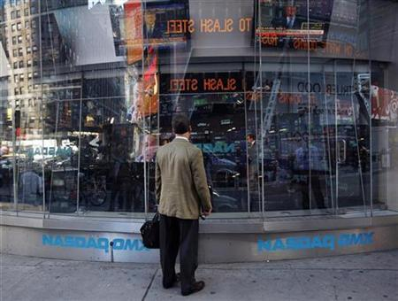 A man stands outside the NASDAQ Market Site as the televised speech by U.S. President George W. Bush is broadcasted in New York October 10, 2008. REUTERS/Shannon Stapleton