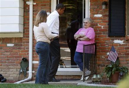 US Democratic presidential nominee Senator Barack Obama (D-IL) (C) speaks to a potential voter as he canvasses a neighbourhood in Holland, Ohio October 12, 2008. REUTERS/Jim Young
