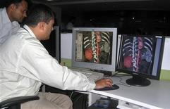 <p>Dr. Arjun Kalyanpur (2nd L) and technologist Jai Singh examine a scan sent from a hospital using the 64-slice CT Scanner at Teleradiology Solutions in the southern Indian city of Bangalore September 5, 2008. REUTERS/Kavita Chandran Budhraja</p>
