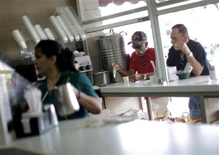 Customers drink coffee at a restaurant in the Little Havana neighborhood of Miami, Florida February 23, 2008. REUTERS/Eric Thayer