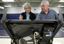 <p>Foto de archivo que muestra a un trabajador electoral y una votante utilizando una máquina de votación electrónica en Grandview Heights, Ohio, 4 mar 2008. En California, cuna de la industria de la computación, la mayoría de los votantes usarán papel y lápiz para emitir sus votos en las elecciones de Estados Unidos del 4 de noviembre. En contraste, los votantes en Brasil e India presionan botones en elecciones completamente electrónicas que llevan la tecnología electoral digital al Amazonas y a los Himalayas. REUTERS/Matt Sullivan/Files (EEUU)</p>