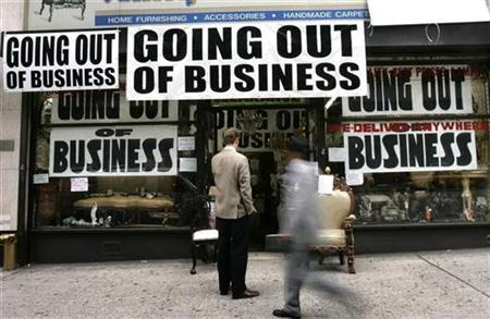 A man stands outside a store advertising that it is going out of business in New York October 6, 2008. REUTERS/Shannon Stapleton