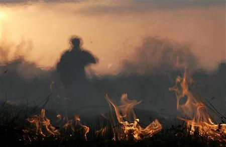 A man watches a brush fire in the forest near the town of Vakarel, about 40km (25 miles) southeast from Sofia, April 22, 2007. REUTERS/Nikolay Doychinov