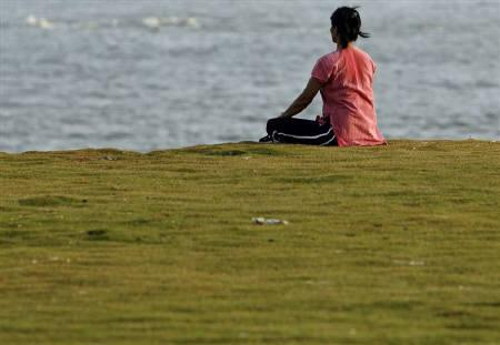 A woman practices yoga by the seaside in Mumbai in this May 6, 2007 file photo. REUTERS/Punit Paranjpe
