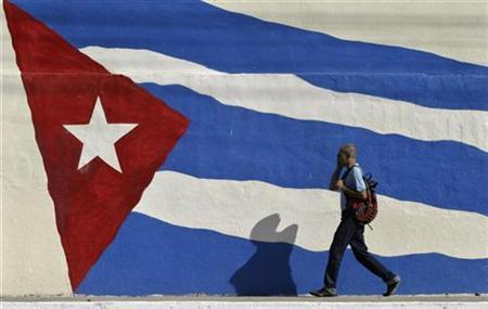 A man walks past a Cuban flag in Havana in this July 25, 2008 file photo.The U.N. General Assembly voted overwhelmingly on Wednesday to urge the United States to lift its 46-year-old embargo against Cuba in a resolution adopted for the 17th consecutive year. REUTERS/Enrique De La Osa