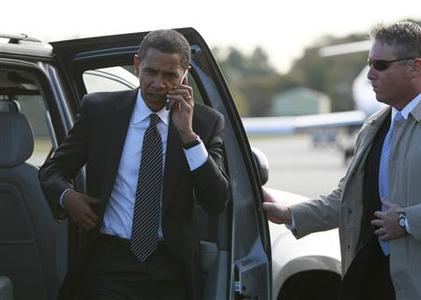 Democratic Presidential nominee Barack Obama talks on his mobile phone as she prepares to step aboard his campaign plane in Norfolk, Virginia, October 29, 2008. REUTERS/Jason Reed