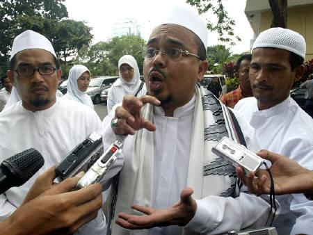 Habib Rizieq Shihab (C), Chief of Islamic Defender Front (FPI), speaks to reporters as he arrives at the Jakarta police headquarters on February 22, 2006. REUTERS/Dadang Tri