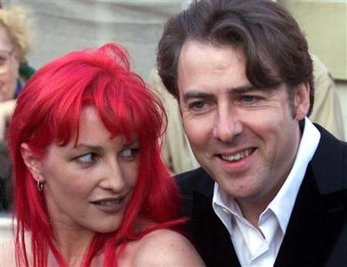 Presenter Jonathan Ross poses for photographers with his wife Jane as he arrives at the Business Design Centre to attend the 51st British Academy Film Awards April 11, 1999. REUTERS/Kevin Coombs