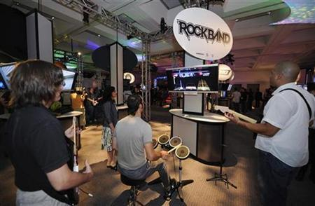 Attendees play the game Rockband by Harmonix at the E3 Media & Business Summit in Los Angeles on July 15, 2008. REUTERS/Phil McCarten