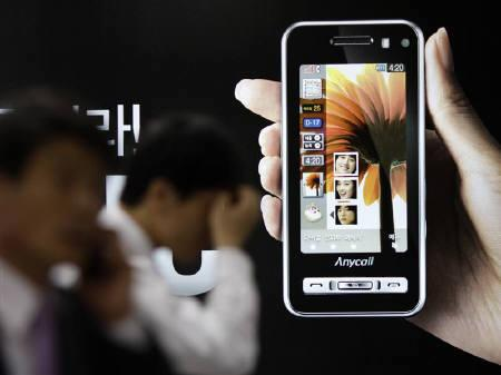 People are seen walking past a sign promoting Samsung Electronics' mobile phones in Seoul in this April 25, 2008 file photo. Samsung Electronics Co Ltd passed Motorola Inc in the third quarter to become the leading cellphone handset vendor in the United States, research firm Strategy Analytics said on Friday. REUTERS/Lee Jae-Won/Files