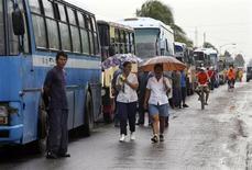 <p>Dei cubani accanto agli autobus destinati a portarli al sicuro a Santa Cruz del Sur, Camaguey, al passaggio dell'uragano Paloma. REUTERS/Enrique De La Osa</p>