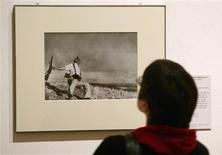 "<p>A visitor looks at the picture ""Death of a militiaman"" taken in 1936 at the Robert Capa Retrospective exhibition in Berlin in this file photo taken January 21, 2005. REUTERS/Arnd Wiegmann/Files</p>"