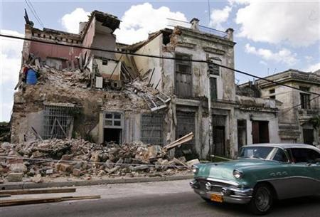A car drives past a building which was damaged by Hurricanes Gustav and Ike, in Havana September 12, 2008. REUTERS/Enrique De La Osa