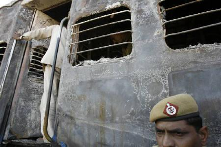 A policeman stands outside a burnt carriage of a Samjhauta Express train in Deewana, near Panipat town in this February 19, 2007 file photo. REUTERS/Desmond Boylan
