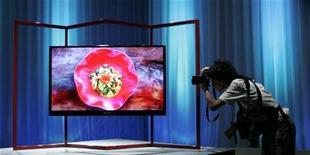 <p>Foto de archivo de un fotógrafo tomando una imagen de un televisor LCD de Sharp durante una conferencia de prensa en Tokio, 22 ago 2007. La japonesa Sharp Corp dijo que está considerando recortar la producción de paneles LCD ya que la crisis económica mundial está afectando a la demanda por éstos televisiones, pero continuará con sus planes de invertir 3.900 millones de dólares para construir una fábrica. REUTERS/Michael Caronna</p>