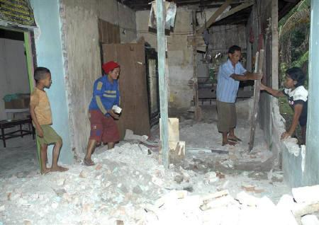 Villagers search for valuable goods at their damaged house at Tolinggula district in north Gorontalo November 17, 2008. Almost 10,000 people have been displaced from their homes following a powerful earthquake that rattled Indonesia's Sulawesi island, a health ministry official said on Tuesday. REUTERS/Aliazh