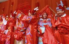 <p>Couples in traditional Chinese wedding costumes take part in a group wedding ceremony in Weifang, east China's Shandong province April 28, 2007. REUTERS/China Daily</p>