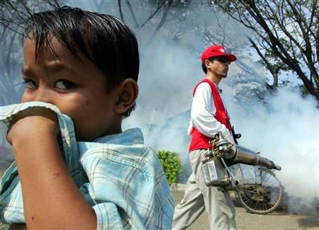 An Acehnese child covers his nose as a South Korean volunteer uses anti-mosquito fog in Banda Aceh, on the Indonesian island of Sumatra, on February 5, 2005. REUTERS/Beawiharta
