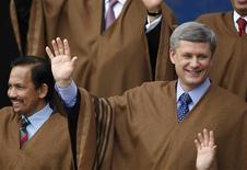 <p>Canada's Prime Minister Stephen Harper (R) stands next to Brunei's Sultan Hassanal Bolkiah while wearing ponchos from Peru for the group photo at the Asia-Pacific Economic Cooperation (APEC) summit in Lima, November 23, 2008. REUTERS/Mariana Bazo</p>