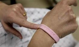 <p>After three operations and four rounds of chemotherapy at Georgetown University Hospital, cancer patient Deborah Charles shows off her breast cancer survivor bracelet during a hospital appointment in Washington May 23, 2007. REUTERS/Jim Bourg</p>
