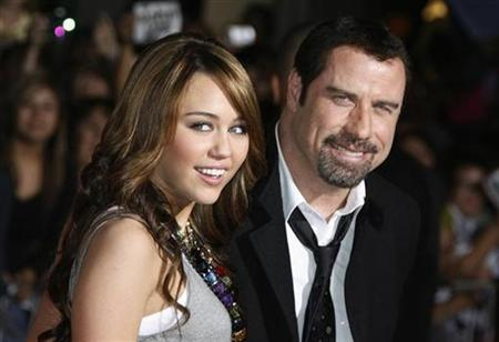 Actors Miley Cyrus and John Travolta (R) pose at the premiere of their animated film ''Bolt'' from Walt Disney Animation Studios in Hollywood November 17, 2008. Cyrus and Travolta provide the voices for two of the characters in the film. REUTERS/Fred Prouser