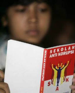 A student reads an anti-graft schoolbook during a trial run of classes at the Pangeran Diponegoro Anti-Corruption School in Jakarta December 4, 2008. REUTERS/Supri
