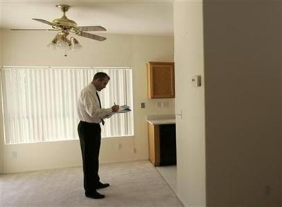 Real estate broker Michael Blower checks a foreclosed home in Stockton for damage and missing appliances May 13, 2008. REUTERS/Robert Galbraith