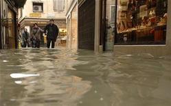 """<p>Turistas caminan en una calle inundada de Venecia 1 dic 2008. Los hoteleros de Venecia, en un esfuerzo por atraer turistas a la ciudad de los canales pese a las inundaciones causadas por los niveles marítimos más elevados en más de dos décadas, ofrecen paquetes especiales """"High Water"""" (marea alta) con botas de goma de regalo. REUTERS/Michele Crosera</p>"""