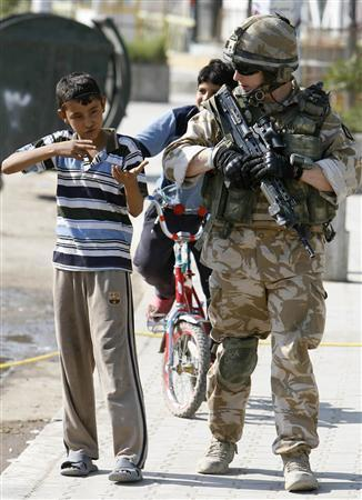 A British soldier looks at a boy pretending to be a soldier holding a weapon during a patrol in Basra, 420 km (260 miles) southeast of Baghdad in this November 25, 2008 file photo. For the first time since the fall of Saddam Hussein in 2003, Iraqis could be seeing election candidates kissing babies and canvassing neighbours when a new polling system comes into force in January 2009. REUTERS/Atef Hassan