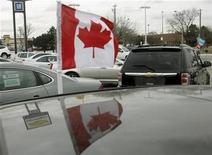 <p>A Canadian flag flies from the window of a General Motors vehicle at a car dealership in Toronto December 12, 2008. Canada's industry minister said on Friday that the federal and Ontario governments have agreed to provide aid to automakers as soon as the U.S. government approves a rescue package. REUTERS/Mike Cassese</p>