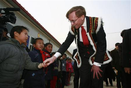 World Bank President Robert Zoellick, dressed in local minority costumes, shakes hands with a primary school student during his visit to the earthquake-hit Leigu County, Sichuan province December 14, 2008. REUTERS/Stringer