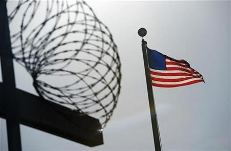 A U.S. flag flies above a razorwire-topped fence at the ''Camp Six'' detention facility at U.S. Naval Station Guantanamo Bay December 10, 2008. REUTERS/Mandel Ngan/Pool