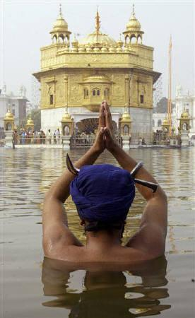A Sikh devotee takes a dip in the pond at the Golden temple in Amritsar November 13, 2008, file photo. A Sikh rights group asked a U.N. human rights committee on Monday to declare that France violated a student's rights by expelling him for wearing a turban and to recommend repealing the law that led to it. REUTERS/Munish Sharma