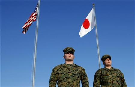U.S. Marines walk past the U.S. and Japanese national flags at Marine headquarters at Camp Foster in Ginowan, southern Japanese island of Okinawa, March 6, 2008. REUTERS/Issei Kato