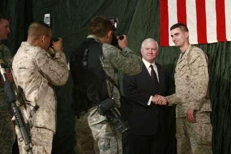 U.S. Defense Secretary Robert Gates poses with a marine after speaking with troops at Kandahar Air field, December 11, 2008. GREUTERS/Scott Olson/Pool