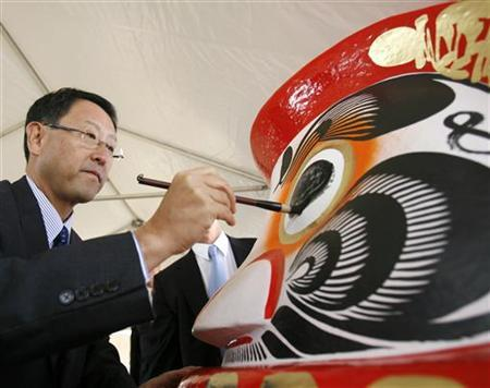 Toyota's Akio Toyoda paints the eye of a Daruma Doll as part of a first steel ceremony, marking the beginning of construction of Canada's first new automobile assembly plant in 20 years, in Woodstock, approximately 100 km west of Toronto , September 21, 2006. REUTERS/J.P. Moczulski