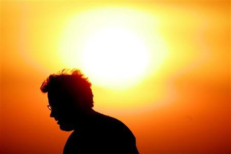 A man walks under the rising sun on Manly Beach in Sydney November 22, 2006. REUTERS/Will Burgess
