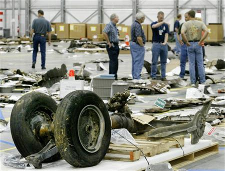 Members of the space shuttle Columbia Reconstruction Team examine pieces of debris from the spacecraft as it is assembled in the RLV Hangar at the Kennedy Space Center in Cape Canaveral, Florida in this May 7, 2003 file photo. REUTERS/Joe Skipper
