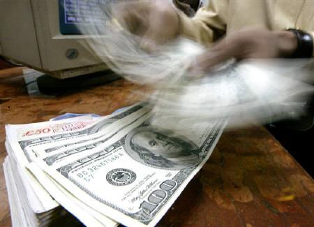 A money changer counts U.S. dollars in Mumbai, in this May 21, 2003 file photo. India's current account deficit swelled to a record $12.54 billion in the September quarter and analysts warned on Wednesday it could balloon further as the world economy slows, putting pressure on the rupee. REUTERS/Arko Datta/Files